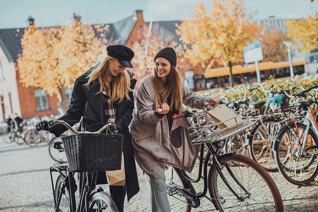 to-glade-mennesker-udendørs-med-cykel