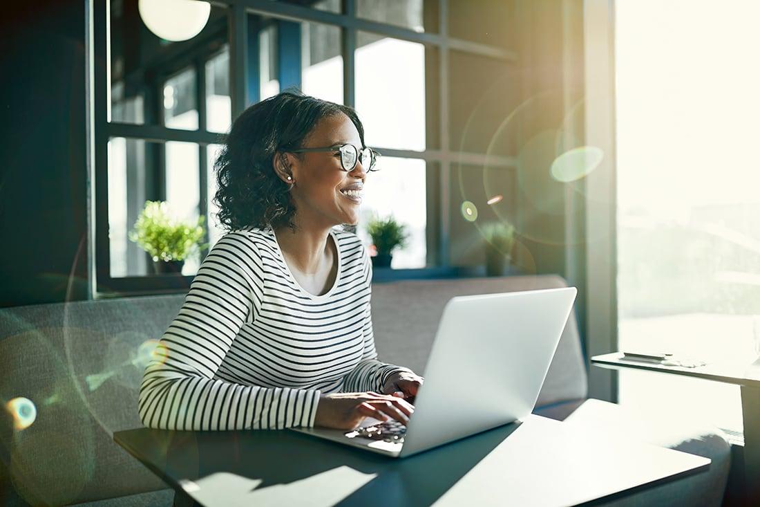 laptop-smillende-kvinde-arbejder-hjemmefra